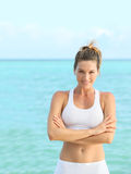 Young woman in a training suit standing by the sea Royalty Free Stock Images