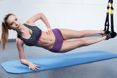 Young woman training with TRX Royalty Free Stock Image