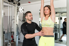 Young Woman Trains Abs Abdominals With Personal Trainer. Personal Trainer Showing Young Woman How To Train On Abs Abdominals In The Gym Stock Photography