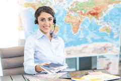 Young Woman Travel Agent Concept. Young woman sitting in office travel agency Stock Photo
