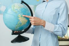 Young female travel agent consultant in tour agency holding globe close-up. Young woman travel agent in tour agency holding globe close-up Royalty Free Stock Photos
