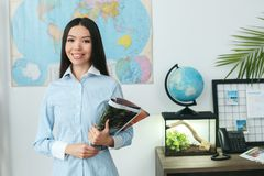 Young female travel agent consultant in tour agency standing looking camera. Young woman travel agent in tour agency standing looking camera holding magazine Royalty Free Stock Photography