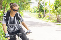 Young woman travel on bicycle. On country road Stock Photo