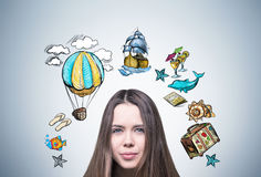 Young woman and travel sketch. Close up of a confused young woman with brown hair standing near a gray wall with a travel sketches around her head stock images