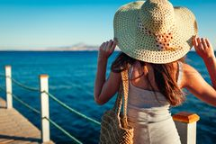 Young woman traveler admiring sea landscape on pier by Red sea. Summer vacation stock photo