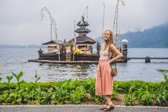 Young woman traveler in the background of Pura Ulun Danu Bratan, Bali. Hindu temple surrounded by flowers on Bratan lake. Bali. Major Shivaite water temple in royalty free stock photo