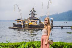 Young woman traveler in the background of Pura Ulun Danu Bratan, Bali. Hindu temple surrounded by flowers on Bratan lake. Bali. Major Shivaite water temple in royalty free stock photos