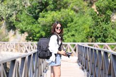 Young woman traveler with backpack enjoying and holding DSLR cam stock photos