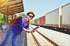 Young woman traveler with backpack and hat holding map. With train background Stock Photo