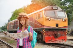 Young woman traveler with backpack and hat at the train station and looking on the map for plan to travel, Travel concept stock photo