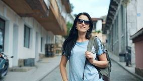 Young woman traveler with a backpack on her shoulder out sightseeing in a ancient city stock video footage