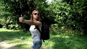 Young woman traveler with backpack hitchhiking on road on summer day. Hitchhiking woman with backpack standing on road. Cute young woman with backpack and stock footage