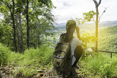 Young Woman Traveler with backpack relaxing outdoor with waterfa. Ll and rocky mountains on background Summer vacations and Lifestyle hiking concept Stock Images