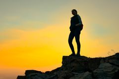 Young Woman Traveler with Backpack Standing on the Top of the Rock at Summer Sunset. Travel and Adventure Concept. royalty free stock photography