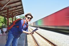 Young woman traveler with backpack standing on train station. With map while waiting for train Royalty Free Stock Image