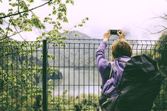 Young woman Traveler with a backpack taking a photo with smart. Young woman Traveler with a backpack taking a photo with smart phone mountain lake. Caucasus Stock Photos
