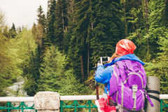 Young woman Traveler with a backpack taking a photo. Young woman Traveler with a backpack taking a photo with smart phone mountain lake. Caucasus, Abkhazia Stock Photos