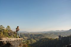 Young woman hiker in the mountains. Young woman traveler with baclpack stand on the cliff in mountains stock images