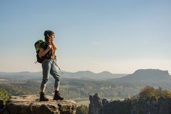 Young woman hiker in the mountains. Young woman traveler with baclpack stand on the cliff in mountains royalty free stock photo