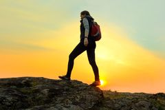 Young Woman Traveler Hiking with Backpack on the Rocky Trail at Warm Summer Sunset. Travel and Adventure Concept. stock photo