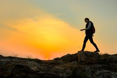 Young Woman Traveler Hiking with Backpack on the Rocky Trail at Warm Summer Sunset. Travel and Adventure Concept. royalty free stock photo