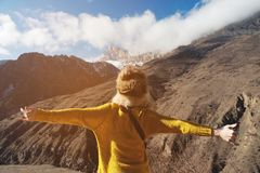 A young woman traveler in a large fur hat and a yellow knitted sweater is standing with arms outstretched in the. Mountains against the background of the epic Royalty Free Stock Photos