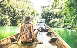 Young woman traveler on longtail boat trip at island hopping tour. Young woman traveler on longtail boat trip in Cheow Lan Lake - Wanderlust and travel concept stock photo