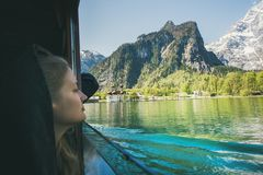 Young woman traveler looking out of window on boat trip at Konigsee Lake in berchtesgaden in Bavaria, Germany. Young woman traveler looking out of window over stock images