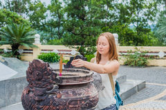 Young woman Traveler praying in polite action with incense sticks at buddhism temple in Vietnam Royalty Free Stock Photos