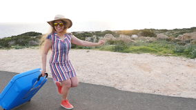 Young woman traveler runs with a suitcase stock video