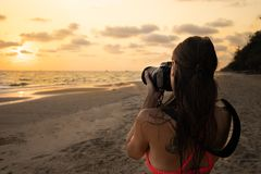 Woman traveler on the shore of a tropical beach photographs the sunset on camera royalty free stock photos