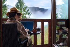 Woman traveler sits at the terrace with a laptop against beautiful mountain scenery during journey. royalty free stock photos