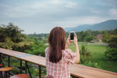 Young lady traveler sitting and relaxing in thai restaurant taking photo with smart phone at mountain. Young woman traveler sitting and relaxing in thai stock photography