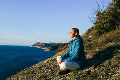 Young woman traveler sitting on top of a cliff and looking at sea Royalty Free Stock Image