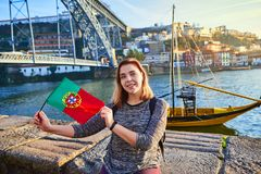 Young woman traveler standing back with portuguese flag, enjoying beautiful cityscape view on Douro river, bridge and boats during royalty free stock photography