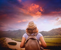 Young woman traveler standing with her back against the backgrou Stock Photo