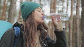 Young woman traveler stands in forest and drinking water from the bottle. Nature pure water concept. Slow motion.  stock video footage
