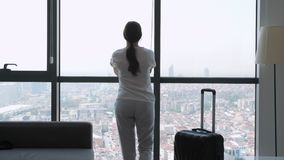 Young woman traveler with suitcase in hotel room with panoramic city view. Young brunette woman traveler with suitcase is entering in hotel room with panoramic stock video