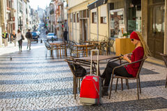 Young woman traveler with a suitcase sitting in a street cafe with a smartphone. Royalty Free Stock Photos