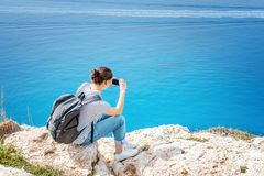 Young woman traveler takes pictures of the seascape on a mobile Royalty Free Stock Photo