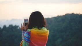 Young woman traveler taking photo with smartphone while standing stock photo