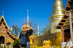 Young woman traveler traveling to Wat Phra Singh temple. This te. Mple contains supreme examples of Lanna art in the old city center of Chiang Mai,Thailand royalty free stock photo