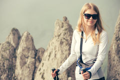 Young Woman Traveler with trekking poles relaxing outdoor Royalty Free Stock Images