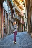 Young woman traveler walking through the old streets of the city in Porto, Portugal royalty free stock image
