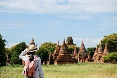 Young woman traveling backpacker with hat, Asian traveler looking Beautiful ancient temples and pagoda, landmark and popular for. Tourist attractions in Bagan royalty free stock photo