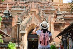 Young woman traveling backpacker with hat, Asian traveler looking Beautiful ancient temples and pagoda, landmark and popular for. Tourist attractions in Bagan royalty free stock images