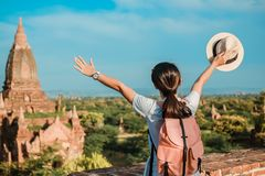 Young woman traveling backpacker with hat, Asian traveler standing on Pagoda and looking Beautiful ancient temples stock photography