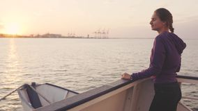 Young woman traveling by boat at sunset or sunrise. In Odessa stock video footage