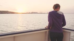 Young woman traveling by boat at sunset or sunrise stock footage