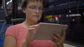 Woman traveling in the city by bus. She using touch pad during the trip. Young woman traveling in the city by bus. She using touch pad during the trip stock video footage